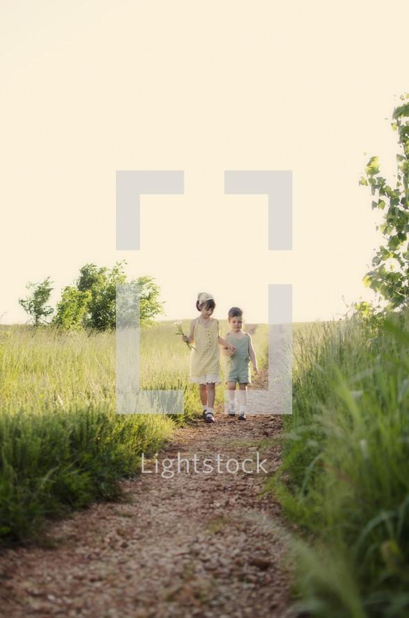 Siblings walking grass trail