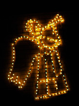 A Christmas Angel made of White Lights outlined against a dark background in the night sky lighting up the horizon to display the Christmas spirit and spread good tidings of joy that a son named Jesus is born who will deliver the world from sin.