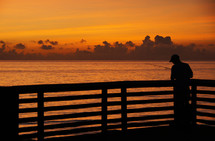 silhouette of a man fishing on a pier