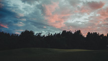 green hills under a sky at sunset