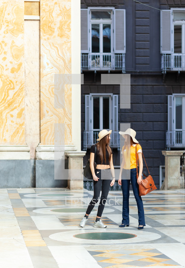 Two young tourists with straw hats in Naples.