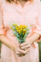 A woman in a peach dress holding a bouquet of yellow flowers.
