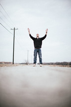 man standing in the middle of a road with his hands raised in worship to The Lord