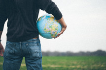 man standing in a field holding a globe