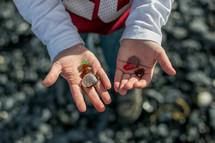 Open hands holding rocks.