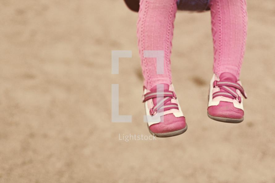 A little girl's legs dangling from a swing.