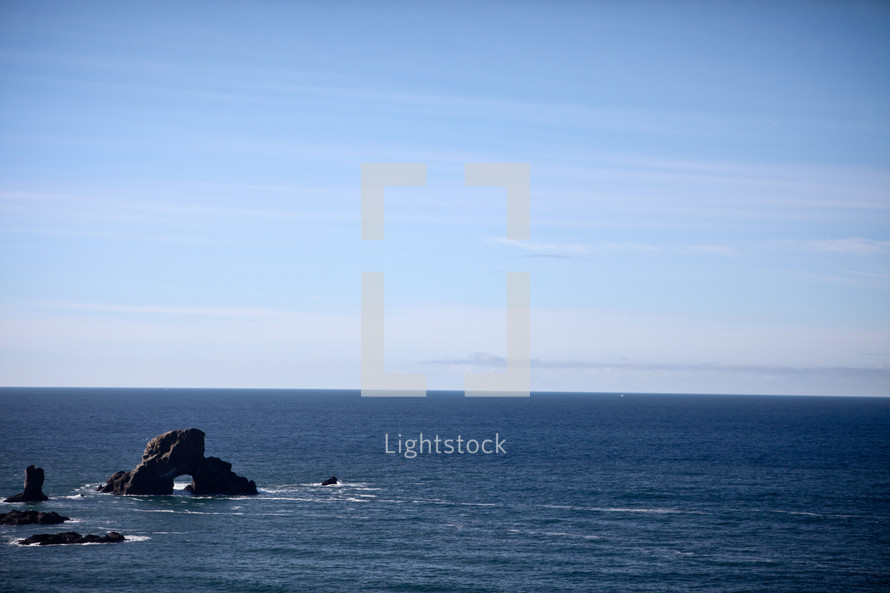 Rocks protruding from water with blue sky