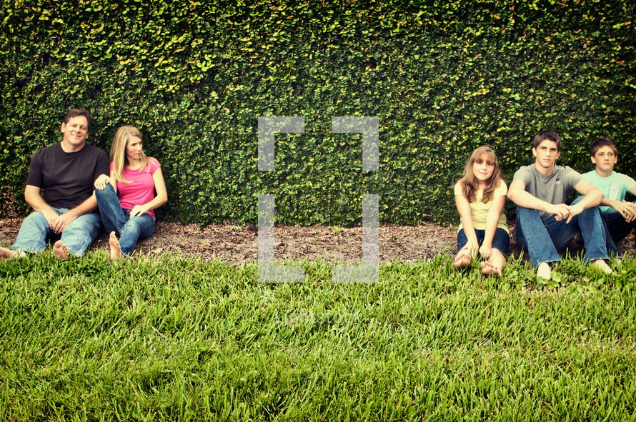Family sitting in front of wall