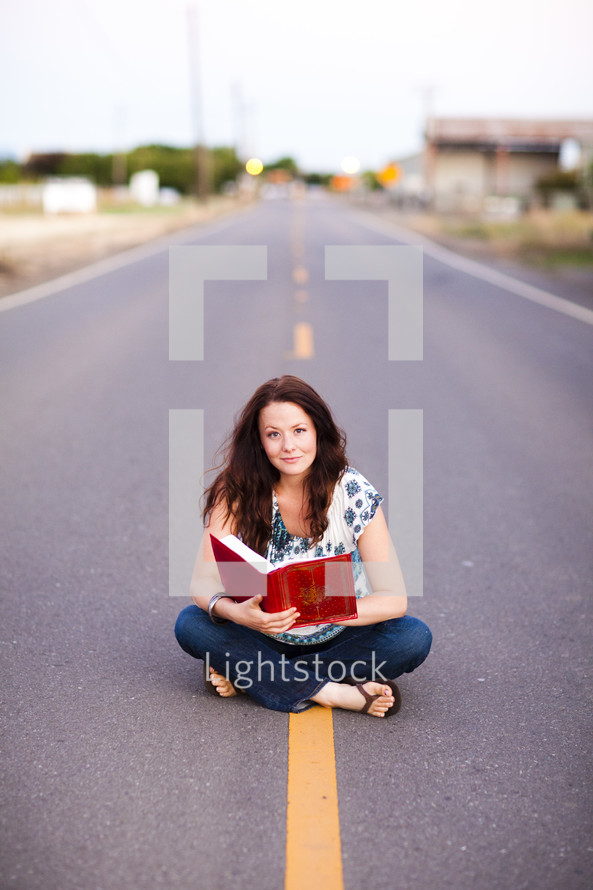 woman sitting in the middle of the street reading bible