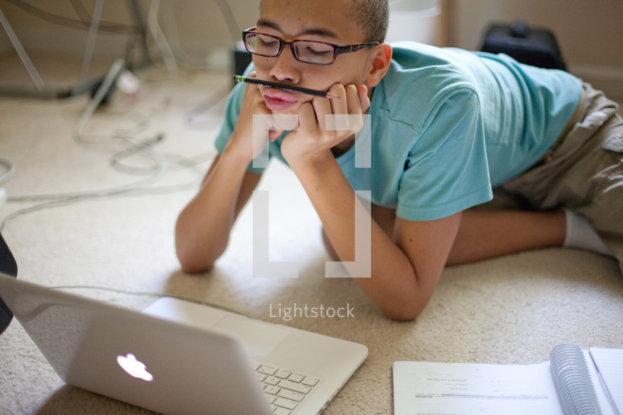 boy resting a pencil under his nose while he works on a computer