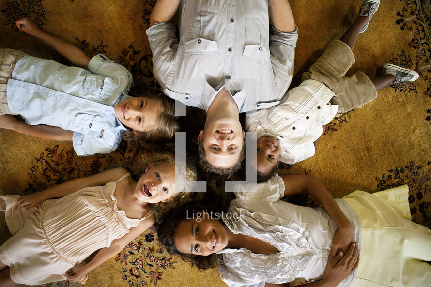 man and four children lying on floor - heads together