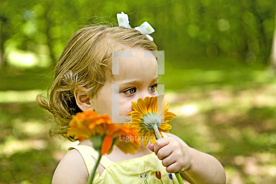Little girl sniffing flower