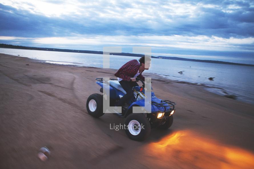 man driving a four wheeler on a beach