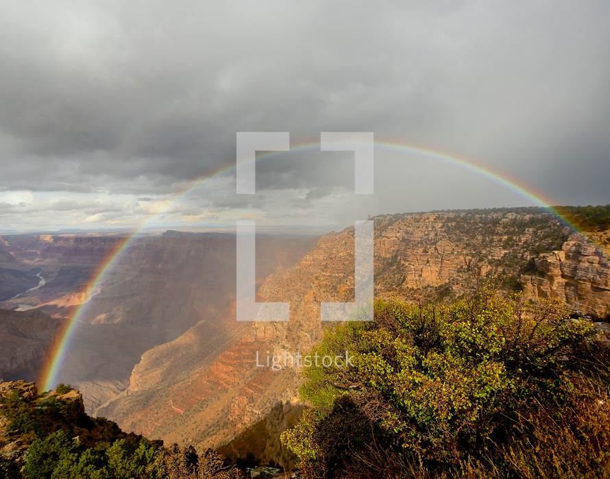 Rainbow over mountain canyon cliff