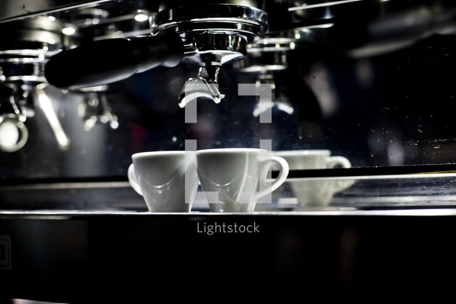 Two coffee cups under an espresso machine