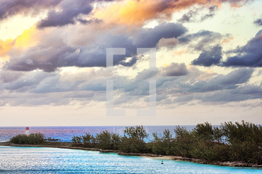 lighthouse on a jetty with colorful clouds in the sky