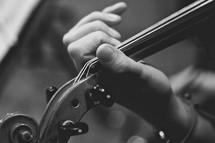 Hand holding neckof violin.
