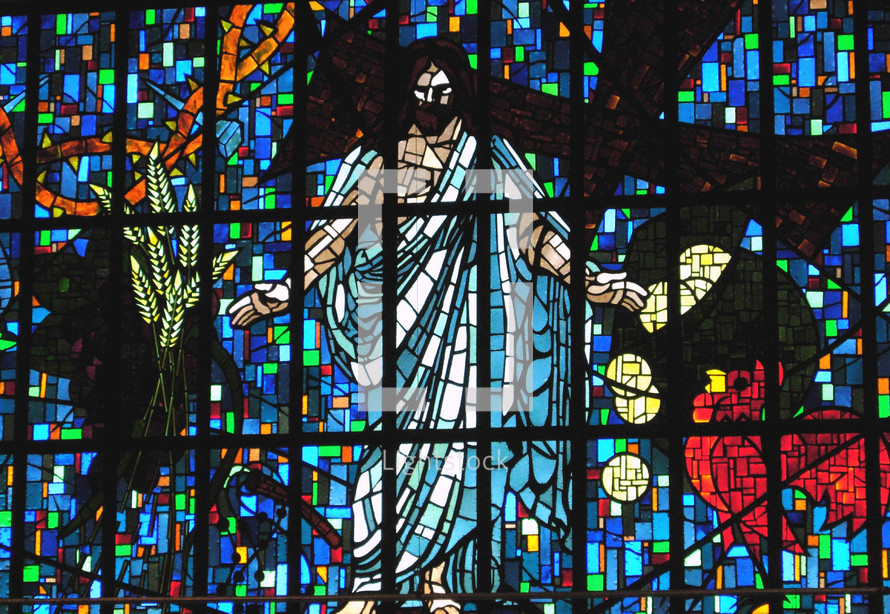 A stained glass window depicting scenes from the life of Christ including Jesus after He was resurrected from the dead, a rooster that crowed three times before Peter denied Jesus, wheat grain and other biblical symbols from the New Testament story of Jesus including the old rugged cross and the crown of thorns that the Roman soldiers pressed on Jesus head.