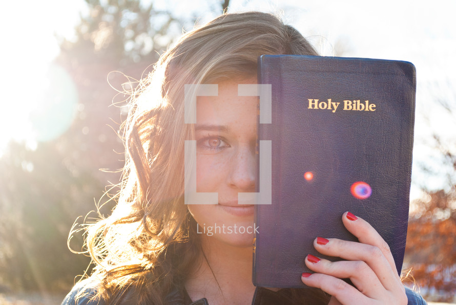 woman holding a Bible in front of half her face