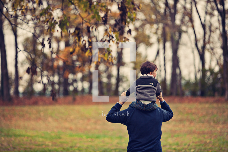 Father walking in tree-lined park with son riding on his shoulders.