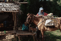 a man loading a basket over the side of a horse