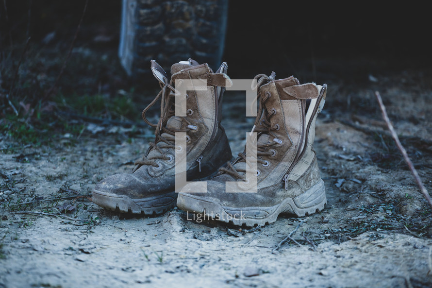 Old brown military boots on mud and grass