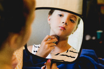 a teen girl putting on make up