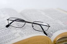 Eye glasses on the pages of an open Bible.