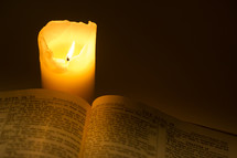 Lit candle burning next to a Bible open to the Book of Acts.