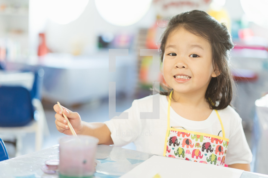 toddler in an apron painting