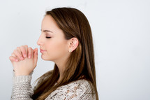 Girl praying with eyes closed and clasped hands.