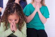 Children praying together.