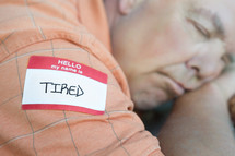 tired name tag - man sleeping