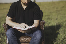 a man reading a Bible while sitting in a leather chair in a field