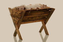 Swaddling clothes in a wooden manger filled with hay.