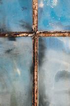 rusty window pane in shape of the cross