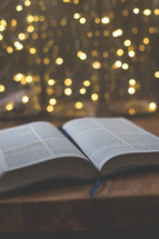 open Bible on a coffee table in front of bokeh lights from a Christmas tree