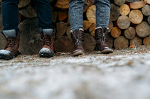 boots and a stack of firewood