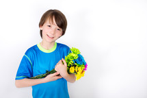 Smiling boy cradling a bouquet of flowers.