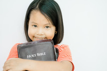 child holding a Holy Bible