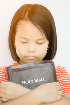 a girl hugging a Bible