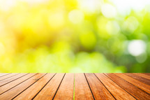 wooden deck and out of focus green plants