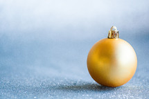 Yellow Christmas orb on a glittering backdrop