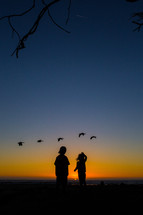 silhouettes of children watching ducks fly