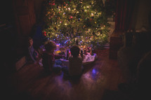 boys playing under a Christmas,tree
