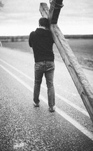 man carrying a large cross along the center lines of a highway - re-enacting Christ's walk, bearing the cross