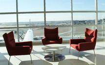 a table and chairs in an airport with a view of the tarmac