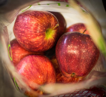 A bag of fresh red apples.