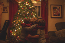 cousins hugging in front of a Christmas tree