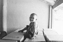a smiling young boy sitting on boxes